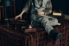 der Junge sitzt auf dem Tisch nahe den selbst gemachten Flugzeugen hergestellt vom Papier und alte Bücher, Vergrößerungsglas und  Stockbild