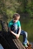 Der Junge sitzt auf den Banken des Flusses im Wald Lizenzfreie Stockfotografie