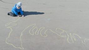 Der Junge sitzt auf der Pflasterung und zeichnet eine lange Schlange der Geldstrafe Stockfoto