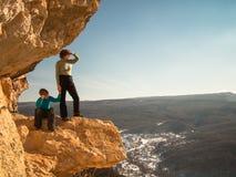 Der Junge sitzt auf einem Felsen nahe der Mutter Stockfotos