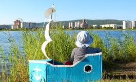 Der Junge sitzt in einem behelfsmäßigen Schiff Stockfotos