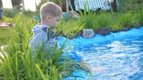 Der Junge sitzt an einem kleinen See Das Kind schafft spritzt vom Wasser mit seinen Füßen Heißer Sommer-Tag Glückliche Kindheit lizenzfreie stockfotografie