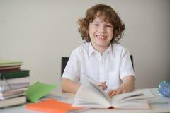 Der Junge sitzt an einem Schreibtisch und tut Hausarbeit Stockfotografie