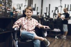 Der Junge sitzt im Friseur ` s Friseursalon Stockfotos