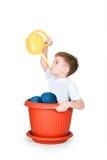 Der Junge sitzt im Großen Flowerpot lizenzfreies stockfoto