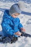 Der Junge sitzt, im Schnee und im Halten eines Schnees und betrachtet ihn und studiert Lizenzfreie Stockbilder