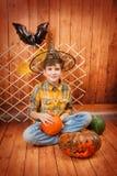 Der Junge sitzt mit Halloweens geschnitztem Kürbis Stockfotos