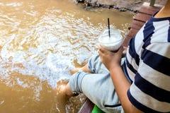 Der Junge sitzt neben dem Fluss Lizenzfreies Stockbild