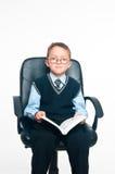Der Junge sitzt und liest das Buch Stockbild