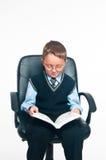 Der Junge sitzt und liest das Buch Stockfotografie