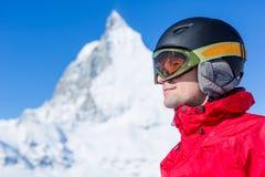 Der junge Skifahrer, der zu einem neuen Tag auf dem Ski bereit ist, neigt sich Lizenzfreie Stockfotos
