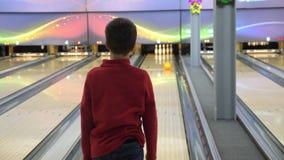 Der Junge spielt Bowlingspiel Er rollt den Ball auf dem Weg und fällt in die Bowlingspielstifte stock video footage