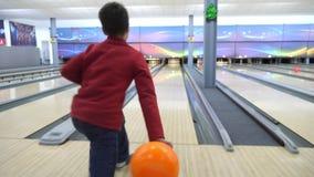 Der Junge spielt Bowlingspiel Er rollt den Ball auf dem Weg und fällt in die Bowlingspielstifte stock footage
