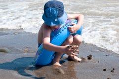 Der Junge spielt Sand auf Seeküste Lizenzfreie Stockbilder