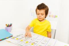 Der Junge spielt in sich entwickelndem Spiel zeigend auf Kalender Stockbild