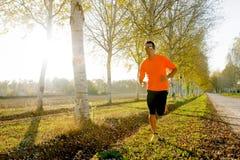 Der junge Sportmann, der draußen in weg von Straßenspur läuft, rieb mit Bäumen Stockbild