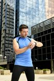 Der junge Sportmann, der Zeit auf chrono Timer-Läufern überprüft, passen das Halten der Wasserflasche nach Schulungseinheit auf Stockfoto