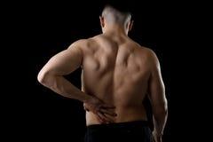 Der junge Sportmann des muskulösen Körpers, der wunde Tiefrückseitentaille hält, erleiden die Schmerz im Athletendruck Lizenzfreie Stockfotos