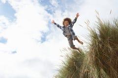 Der Junge springend über Düne stockbilder
