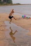 Der Junge springend über Pfütze Stockfotos