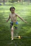 Der Junge springend über Rasensprenger Stockfotos