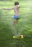 Der Junge springend über Rasensprenger Lizenzfreies Stockfoto