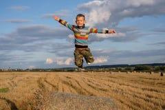 Der Junge springend auf den Strohballen Stockbild