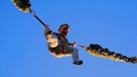 Der Junge springend auf eine Trampoline mit elastischen Seilen Kleines Kind, das auf die Trampoline springt Federelement, springe