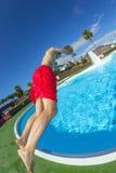 Der Junge springend in das blaue Pool Lizenzfreie Stockfotos