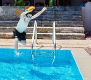 Der Junge springend in das Pool Lizenzfreie Stockfotos