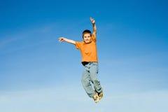 Der Junge springend in den Himmel lizenzfreies stockfoto