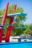 Der Junge springend in ein Pool Lizenzfreie Stockbilder