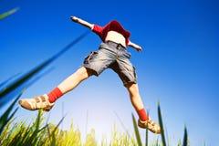 Der Junge springend gegen den blauen Himmel Lizenzfreie Stockfotografie