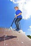 Der Junge springend mit seinem Roller Stockbilder