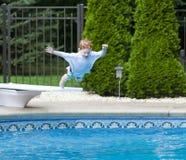 Der Junge springend in Pool Lizenzfreie Stockfotos