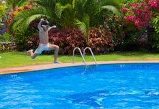 Der Junge springend in Pool Stockbild
