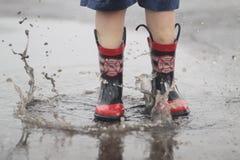 Der Junge springend in Regen-Pfütze Lizenzfreie Stockfotos