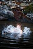 Der Junge springend in See Stockfotos