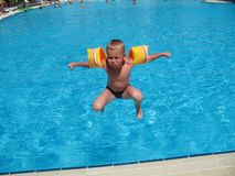 Der Junge springend in Swimmingpool Stockfotos