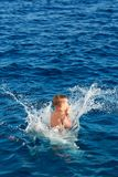 Der Junge springend in Wasser Stockbild