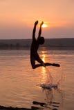 Der Junge springend in Wasser auf Sonnenuntergang Lizenzfreies Stockfoto