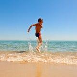 Der Junge springend zum Meer Lizenzfreies Stockbild