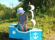 Der Junge steht in einem behelfsmäßigen Schiff Lizenzfreie Stockfotos