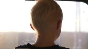 Der Junge steht in einem Zug am Fenster stock footage