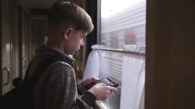 Der Junge steht am Zugfenster mit einer Tablette in seinen Händen Reise durch Serie Ferientourismus, reisend die Welt stock footage