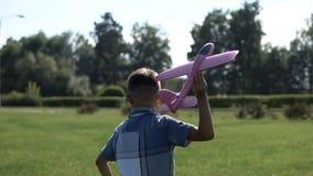 Der Junge stellt eine Spielzeugfläche im Park im sonnigen Wetter an Langsame Bewegung stock video
