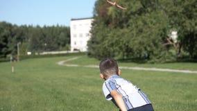 Der Junge stellt eine Spielzeugfläche im Park im sonnigen Wetter an Langsame Bewegung HD stock footage