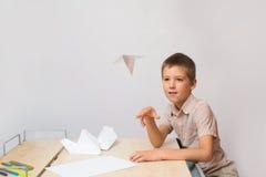 Der Junge stellte eine Papierfläche her und ließ sie laufen Stockfotos