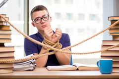 Der junge Student gezwungen zu studieren gebunden stockfotos