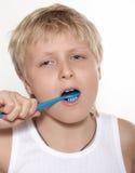 Der Junge säubert Zähne eine Zahnbürste. Ein Hintergrundweiß Stockbild